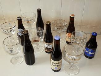 trappistenbierflesjes en glazen op witte tafel